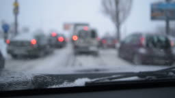 View through windshield on defocused scene on snowy city road