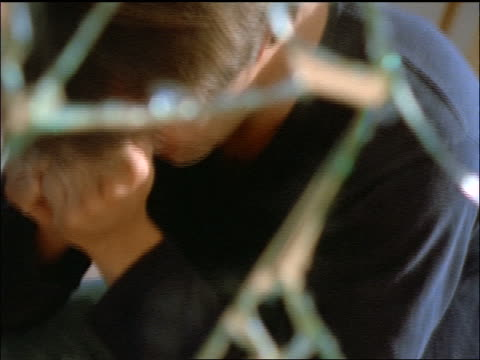 view thru broken glass of young male holding face in hands / drug addict - 精神障害点の映像素材/bロール