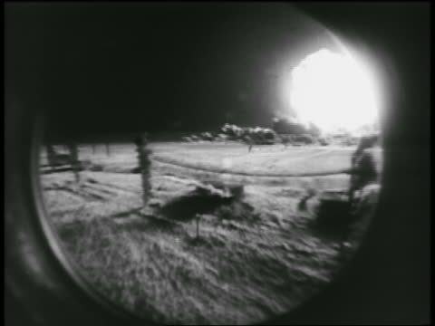 B/W 1955 view thru circular window of atomic bomb explosion during test / Nevada / documentary