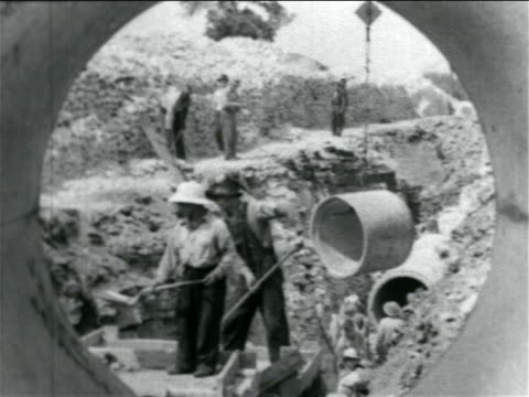 b/w 1934 view thru pipe of men working in wpa sewage construction project / documentary - new deal video stock e b–roll