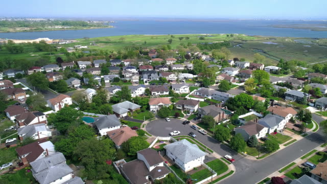 view to a wealthy residential district in oceanside, queens, new york city, with houses with pools on backyards and piers with boats along the channels. aerial drone video with the backward camera motion. - long island video stock e b–roll