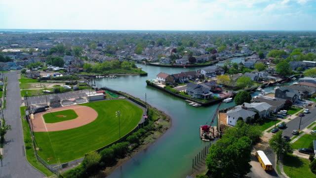 vidéos et rushes de vue sur un quartier résidentiel riche à oceanside, queens, new york city, avec des maisons avec des piscines sur les arrière-cours et les jetées avec des bateaux le long des canaux. vidéo de drone aérien avec le mouvement de caméra arrière. - baie eau