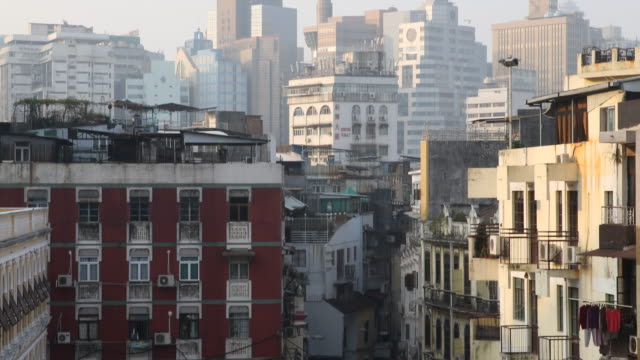 A view to Macau's urban landscape in the early morning with the mixture of modern architecture of Casinos highrise in the background and simple...