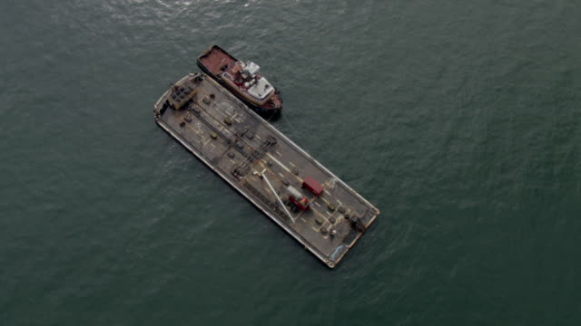 WS AERIAL View top over calm bay waters and flatbed boat and tugboat in Naknek District / Alaska, United States