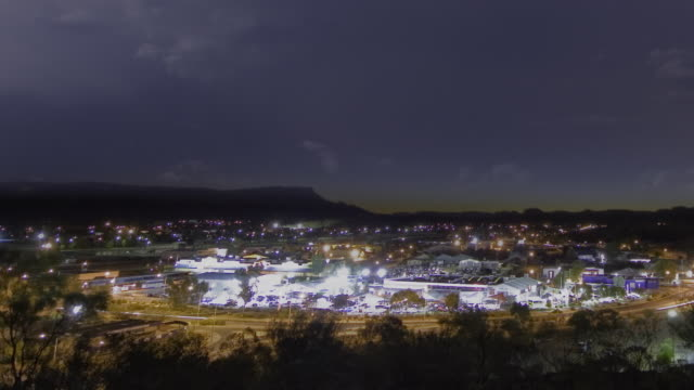 ws pan t/l view towards alice springs at dusk, as night falls  thunderstorm with lightning flashing over city / alice springs, northern territory, australia. - town stock videos & royalty-free footage