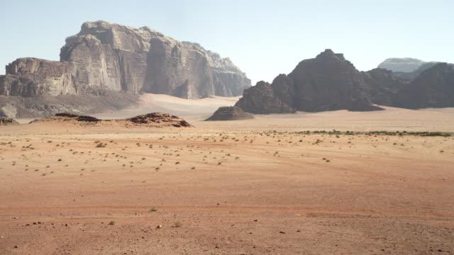 vídeos y material grabado en eventos de stock de ws ts view two camel grazing and rock mountain / wadi rum, jordan - paisaje árido