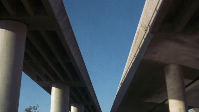 view underneath raised highway with shadows of traffic driving - elevated road stock videos & royalty-free footage