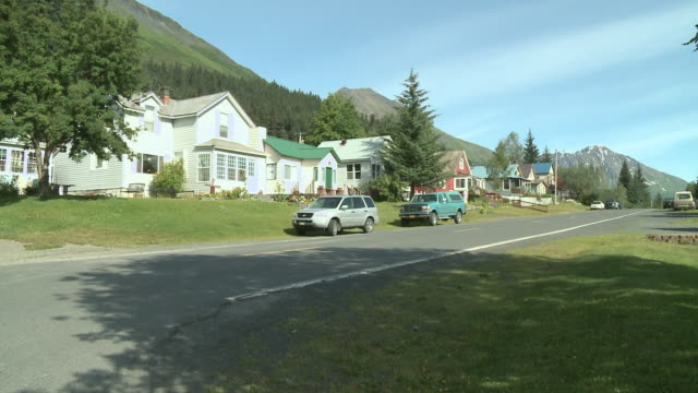 """""""view up 2nd avenue with picturesque wooden houses, with different coloured roofs, national flag of the united states of america waving in the wind outside one house, no cars pass, sun shining, forest in background, seward, kenai peninsula, alaska."""" - kenai peninsula stock videos & royalty-free footage"""