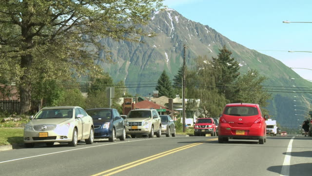 """view up 3rd avenue past jefferson street, cars pass in both directions, parked cars, green trees and snow capped marathon mountain in background. seward, kenai peninsula, alaska."" - kenai stock videos & royalty-free footage"