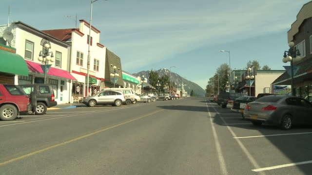 """""""view up 4th avenue, colourful shops and buildings, parked cars and marathon mountain with snow in background, two cars pass in opposite directions, seward, kenai peninsula, alaska."""" - kenai peninsula stock videos & royalty-free footage"""