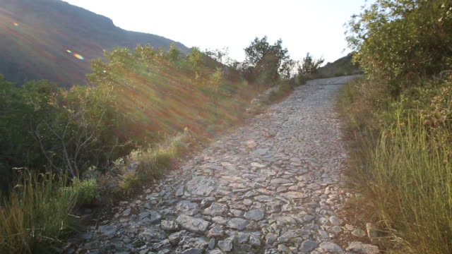 view up cobblestone path, hills distant, sunrise - cobblestone stock videos & royalty-free footage