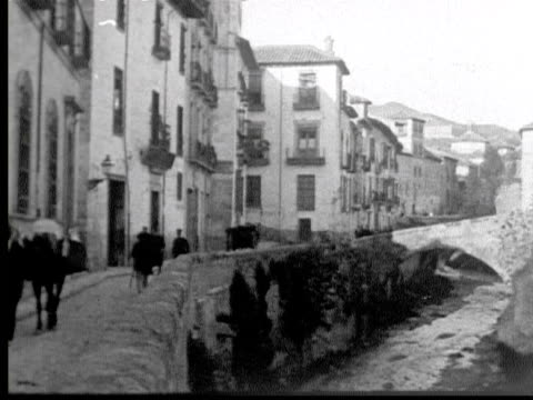 1925 B/W WS PAN View up river bed running through medieval village w/ road alongside / Granada, Spain