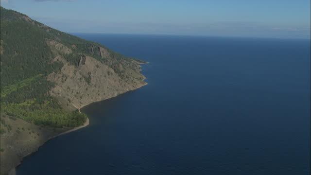 WS POV AERIAL View Wooded cliffs bordering Lake Baikal / Lake Baikal, Siberia, Russia