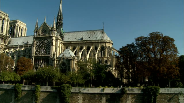 Viewed from across the Seine, pedestrians walk by the Notre Dame Cathedral in Paris, France.