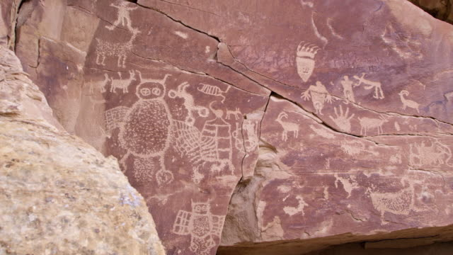 vídeos de stock, filmes e b-roll de viewing petroglyph panel while it is lightly snowing in the utah desert - anasazi