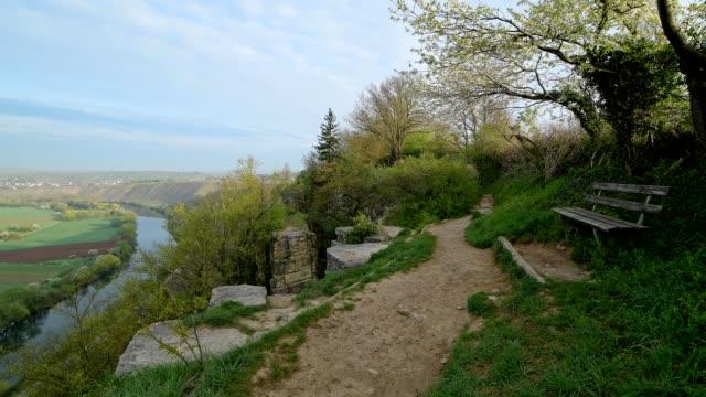 viewpoint on neckar river with bench and path in spring, hessigheim, felsengärten, river neckar, baden-württemberg, germany - neckar river stock videos & royalty-free footage