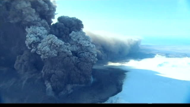 VIEWs / AERIALs of erupting volcano under the Eyjafjallajokull glacier showing rising voluminous ash cloud