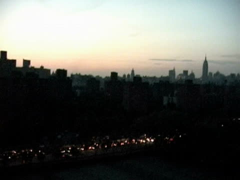 views at dusk from bridge fdr empire state bldg boat on river bqe manhattan skyline all dark except for car lights - power cut stock videos & royalty-free footage
