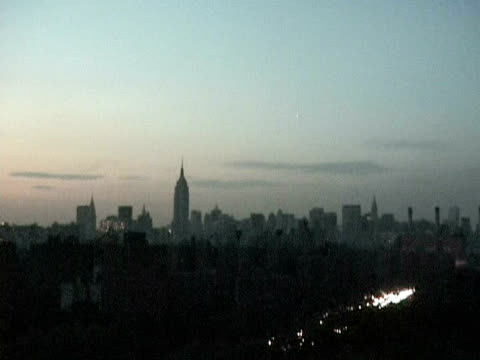 views at dusk from bridge fdr empire state bldg boat on river bqe manhattan skyline all dark except for car lights - 2003年点の映像素材/bロール