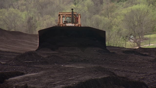 views of a coalmine where coal is scooped by a digger and dropped into a machine followed by smoke rising out of chimneys - ausschöpfen stock-videos und b-roll-filmmaterial