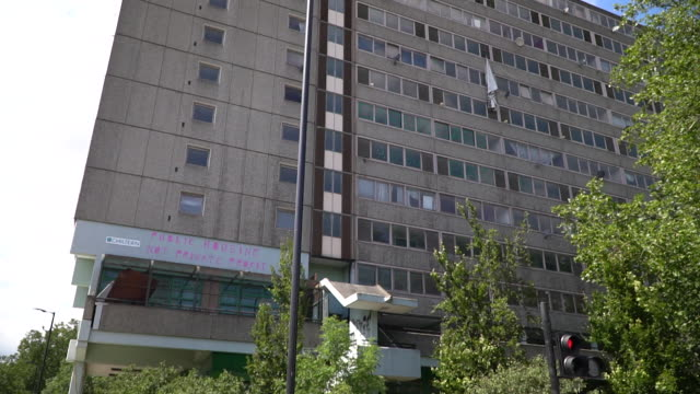 views of a council house block with graffiti saying 'public housing not private profit' written above the entrance - council flat stock videos & royalty-free footage