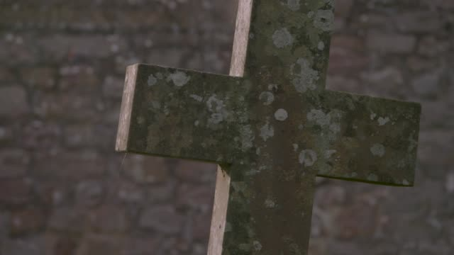 Views of a cross-shaped gravestone in a churchyard