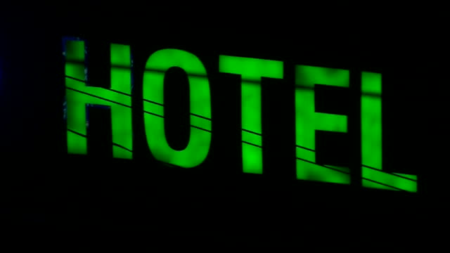 Views of a 'Hotel' sign changing colour