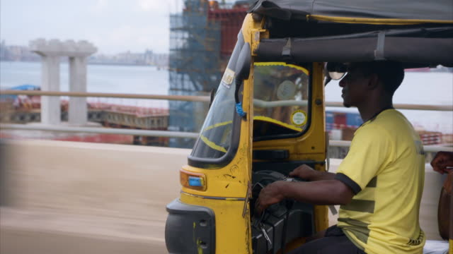 views of a man using a tuk tuk in lagos - risciò video stock e b–roll