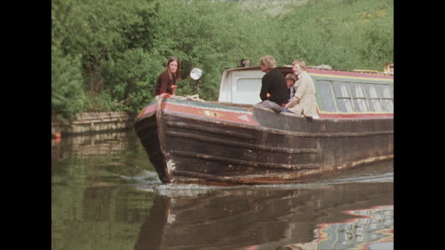 views of a narrowboat moving along the river - anno 1975 video stock e b–roll