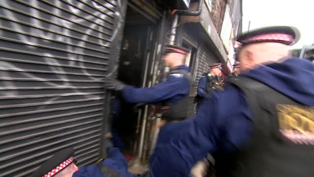 views of a police raid on a counterfeit clothing manufacturer - デザイナー服点の映像素材/bロール