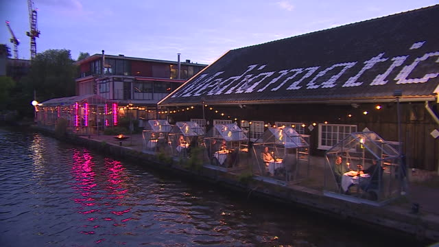 views of a restaurant in amsterdam where diners can eat outside in greenhouses to maintain coronavirus social distancing - gewächshäuser stock-videos und b-roll-filmmaterial