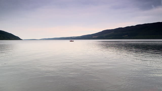 Views of a rowboat on the calm waters of Loch Ness with Urquhart Castle in the foreground