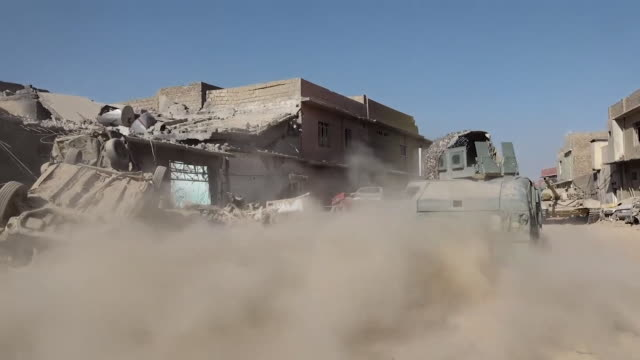 Views of an armoured vehicle and rising smoke in the city of Mosul