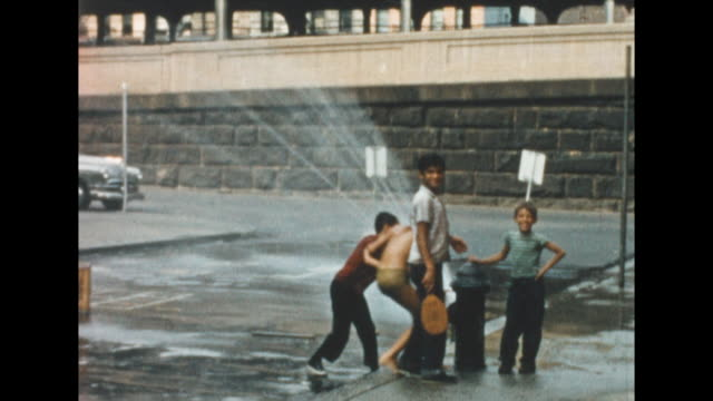 vídeos y material grabado en eventos de stock de views of boys in new york's lower east side cooling off with an opened fire hydrant. the boys dance in the water and spray each other. from the... - boca de riego