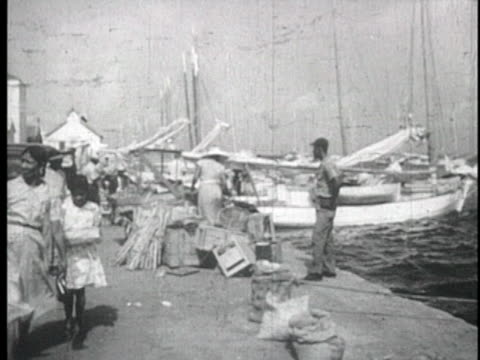 vidéos et rushes de views of busy small harbor small boats tied to dock people selling wares on the dock - bahamas