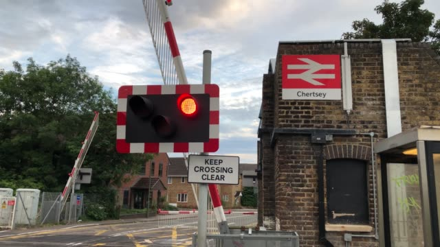 views of chertsey train station barriers drop down where bullied 14 year old school boy sam connor lay down on the tracks and was killed by moving... - railway station stock videos & royalty-free footage