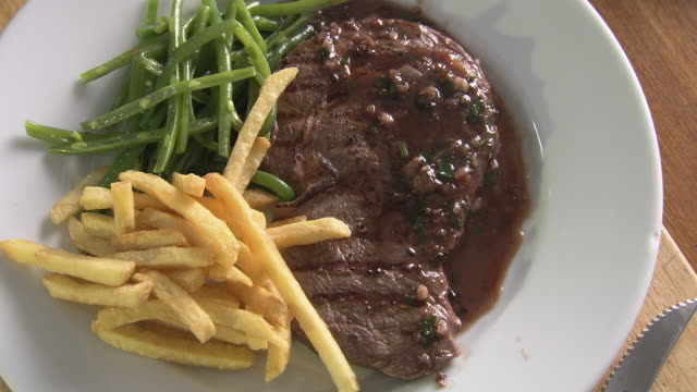 vidéos et rushes de views of classic french dish steak frites - assiette