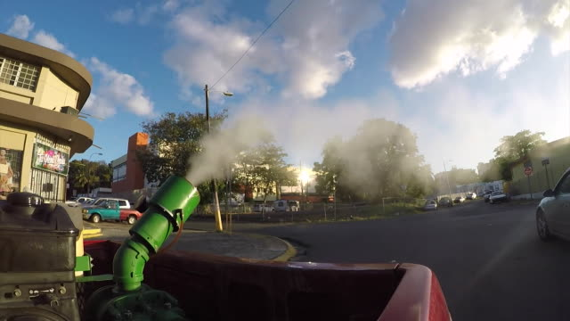 Views of fumigators spraying insecticide on a street in Puerto Rico