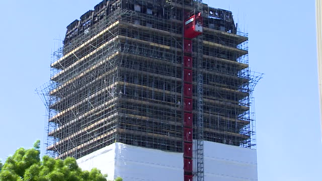 Views of Grenfell Tower with a white sheet being built to cover it