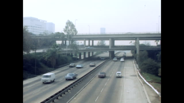 / views of highways systems cars smog and buildings in los angeles los angeles freeways and traffic on january 01 1970 in los angeles california - 1969年点の映像素材/bロール