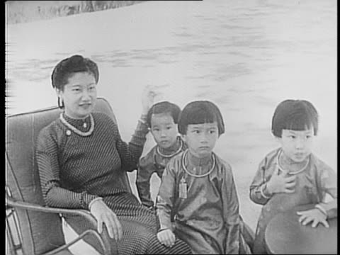 vidéos et rushes de views of mountains forested areas water / modern home empress of annam sits with her three children closeup of her and children's faces /... - chiffon