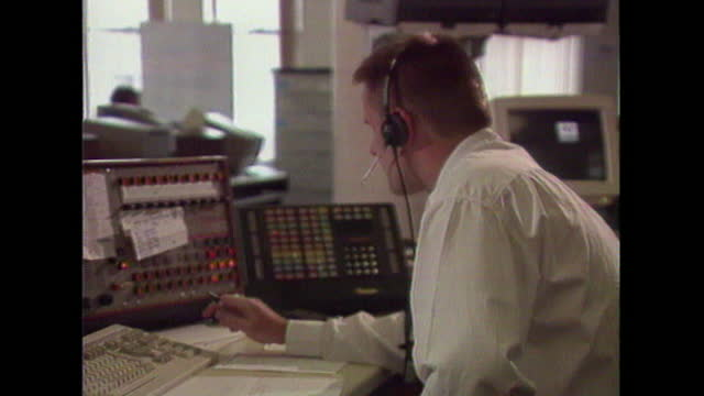 views of operators taking calls and using switchboards in a police control room, uk; 1993. - adult stock videos & royalty-free footage
