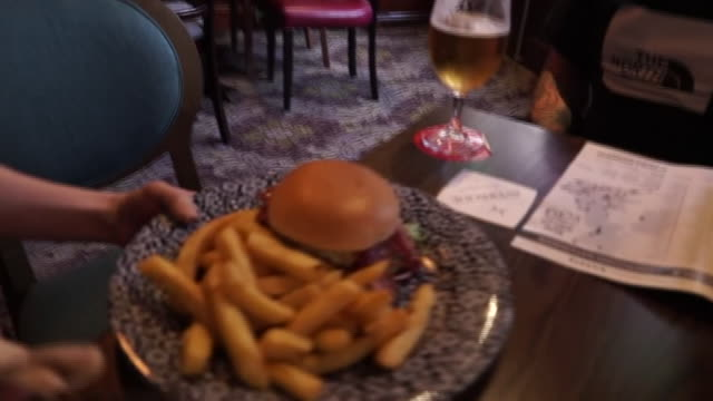views of people eating burgers and chips in a pub - beer alcohol stock videos & royalty-free footage