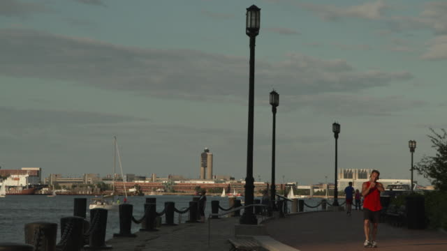 Views of people using a footpath around Boston Harbor, Massachusetts, during a summer's evening, USA.
