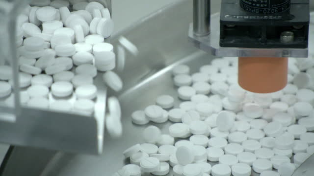 vídeos de stock, filmes e b-roll de views of pills on a conveyor at a manufacturing plant - remédio