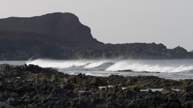 views of rocky coastline on volcanic island, japan - gezeiten stock-videos und b-roll-filmmaterial