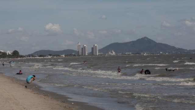 views of saen beach north of pattaya chonburi province thailand on may 29 2015 shots wide shots of bathers walking along the beach and the waves... - pattaya stock videos & royalty-free footage