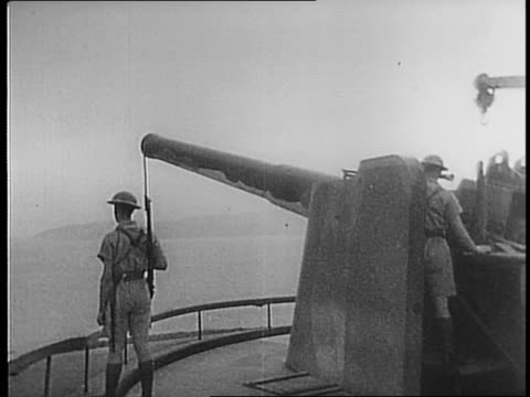 Views of ships in water panning shots / Navy soldiers walk by camera in uniform / Canadian miners building defenses inside the rock using cement and...