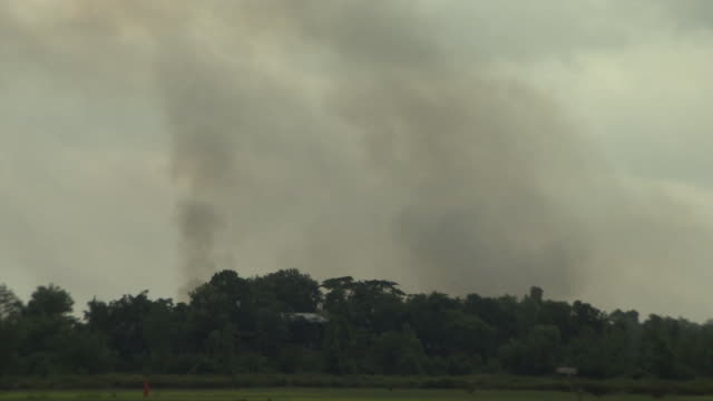 Views of smoke rising from a Rohingya village as seen from the Bangladesh side of the border with Burma