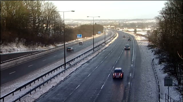 stockvideo's en b-roll-footage met lancashire int vehicles along m6 motorway with snow on ground / cars past turn off to m56 'skelmersdale liverpool southport / high angle view traffic... - southport engeland